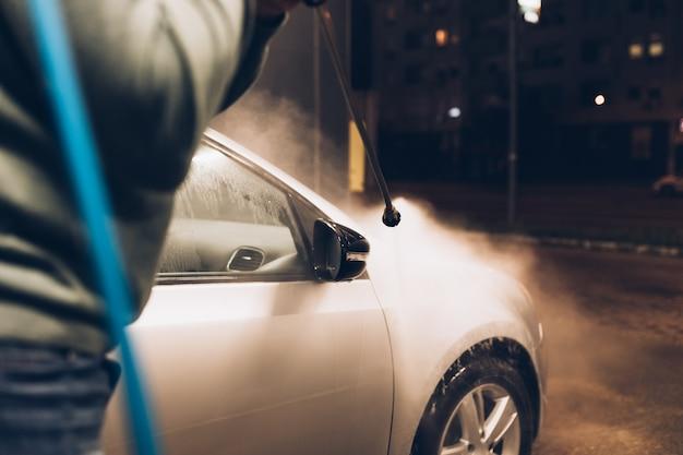 Starszy mężczyzna myjący samochód wieczorem na myjni samochodowej przy użyciu wody pod wysokim ciśnieniem pressure