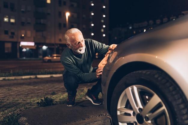 Starszy mężczyzna myjący samochód wieczorem na myjni samochodowej