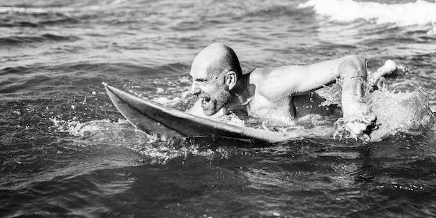 Starszy mężczyzna na desce surfingowej
