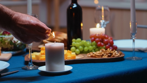 Starszy mężczyzna na emeryturze zapalając świecę czeka na żonę na romantyczną kolację. starszy mąż przygotowuje świąteczny posiłek ze zdrowym jedzeniem na obchody rocznicy, siedząc przy stole w kuchni.