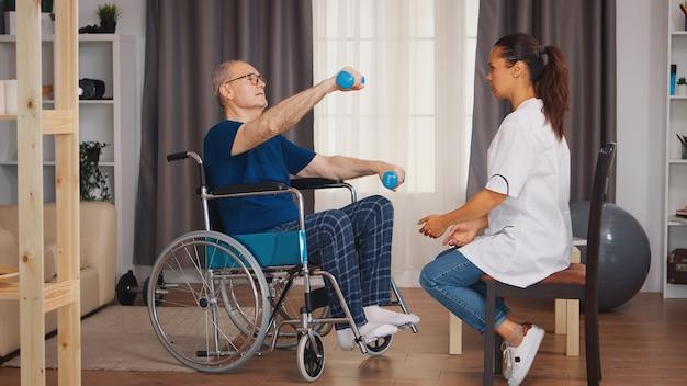 Starszy mężczyzna na wózku inwalidzkim ćwiczący podczas rehabilitacji przy wsparciu lekarza. osoba starsza niepełnosprawna niepełnosprawna z pracownikiem socjalnym w okresie rekonwalescencji terapia rehabilitacyjna fizjoterapia pielęgniarki opieki zdrowotnej