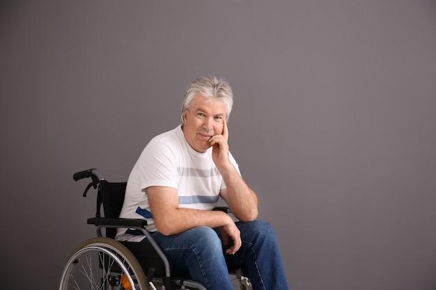 Starszy mężczyzna na wózku inwalidzkim na szarej powierzchni