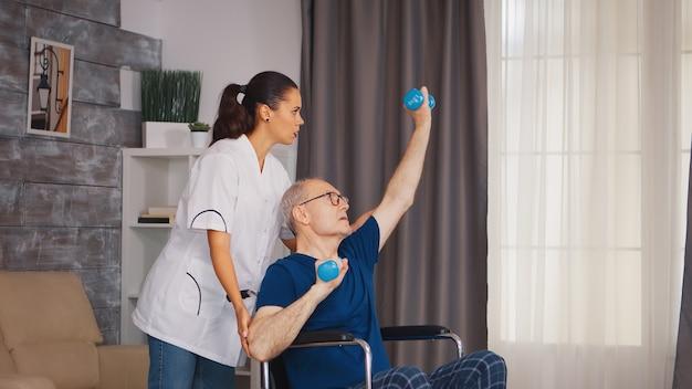 Starszy mężczyzna na wózku inwalidzkim robi profesjonalną regenerację kontuzji. osoba starsza niepełnosprawna niepełnosprawna z pracownikiem socjalnym w okresie rekonwalescencji terapia pomocnicza fizjoterapia system opieki zdrowotnej dom spokojnej starości