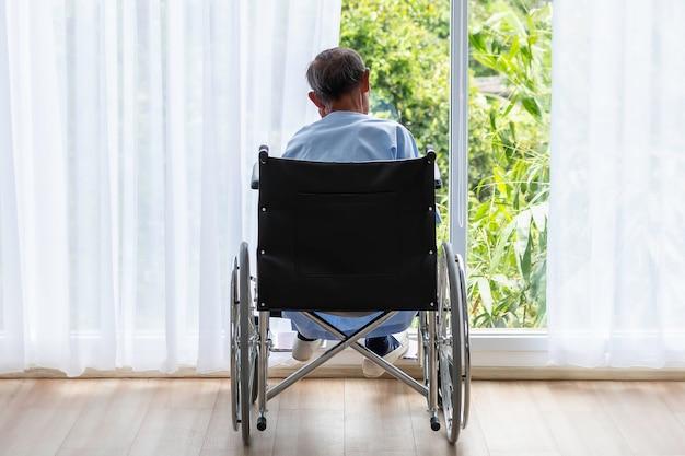 Starszy mężczyzna na wózku inwalidzkim z plecami w szpitalu.