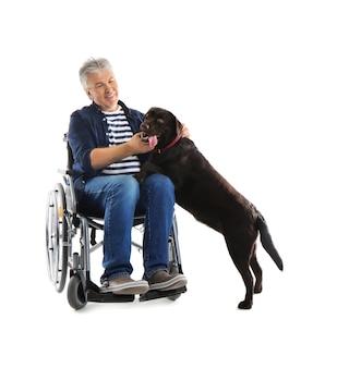 Starszy mężczyzna na wózku inwalidzkim z psem na białym tle