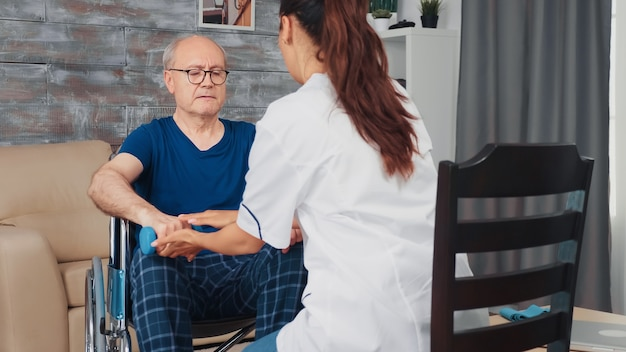 Starszy mężczyzna na wózku inwalidzkim z urazem mięśni robi fizykoterapię z pielęgniarką. niepełnosprawna niepełnosprawna osoba starsza powracająca do zdrowia profesjonalna pomoc pielęgniarska, leczenie w domu spokojnej starości i rehabilitacja