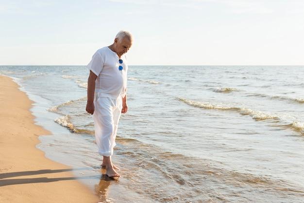 Starszy mężczyzna na zewnątrz, ciesząc się na plaży