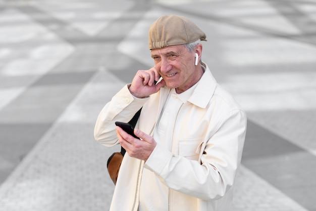 Starszy mężczyzna na zewnątrz w mieście za pomocą smartfona z wkładkami dousznymi