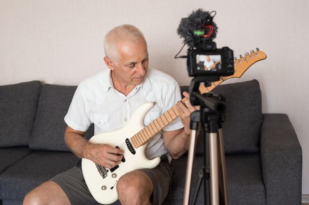 Starszy mężczyzna nagrywa teledysk, lekcje domowe lub piosenkę, gra na gitarze lub prowadzi program telewizyjny w internecie, siedząc na kanapie w domu.