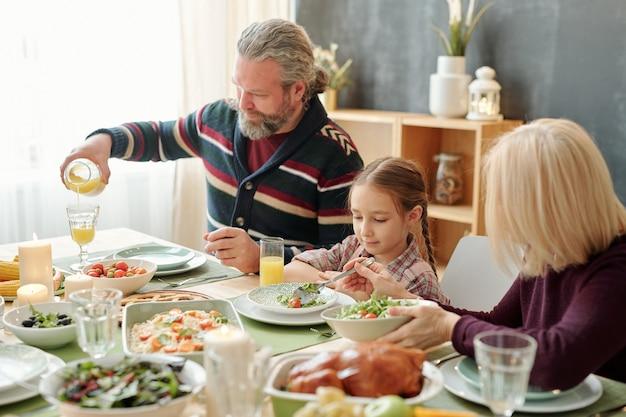 Starszy mężczyzna nalewa sok pomarańczowy do szklanki przy świątecznym stole podczas rodzinnego obiadu z żoną i śliczną wnuczką