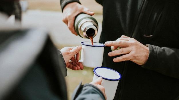 Starszy mężczyzna nalewający poranną kawę z termosu