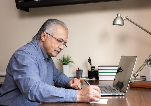Starszy mężczyzna nauczy się korzystać z komputera. stary człowiek w szkle i niebieskiej koszuli przy użyciu komputera przenośnego do nauki online w domowym biurze