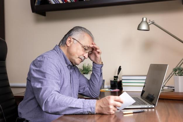 Starszy mężczyzna nauczy się korzystać z komputera. stary mężczyzna w szkle i niebieskiej koszuli czyta instrukcje dotyczące pracy z komputerem przenośnym do nauki online w biurze domowym