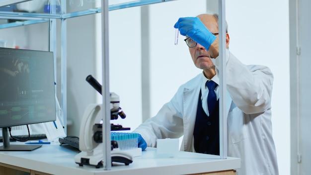 Starszy mężczyzna naukowiec robi badania analizujące ciecz w probówce w nowocześnie wyposażonym laboratorium. wieloetniczny zespół badający ewolucję szczepionek przy użyciu zaawansowanych technologii do opracowania leczenia przeciw covid19