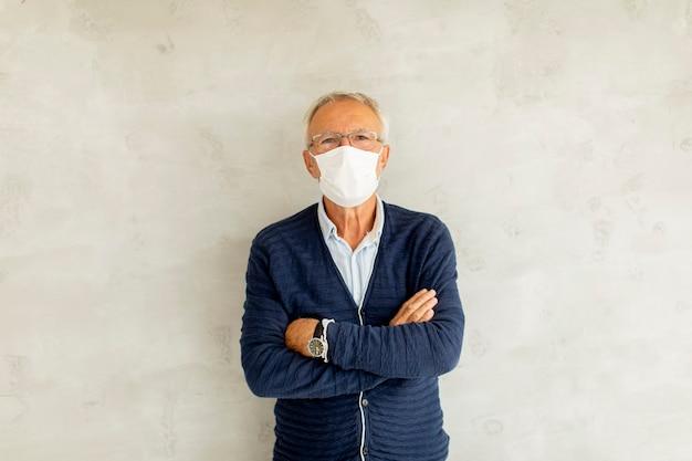 Starszy mężczyzna nosi maskę ochronną na twarz i stoi przy ścianie z rękami skrzyżowanymi