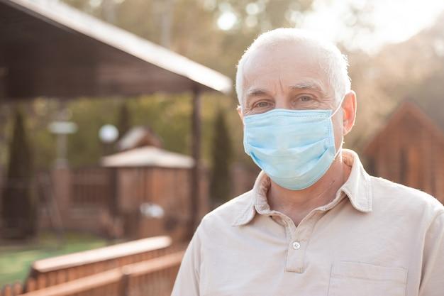 Starszy mężczyzna nosi maskę ochronną przed chorobami zakaźnymi i grypą, kwarantanna koronawirusa.