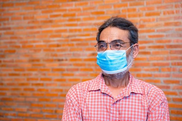 Starszy mężczyzna nosi maskę ochronną przed chorobami zakaźnymi i grypą