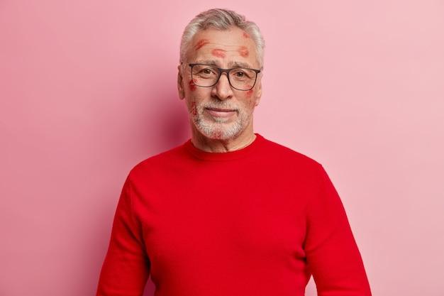 Starszy mężczyzna o plamy szminki na twarzy i ubrany w czerwony sweter
