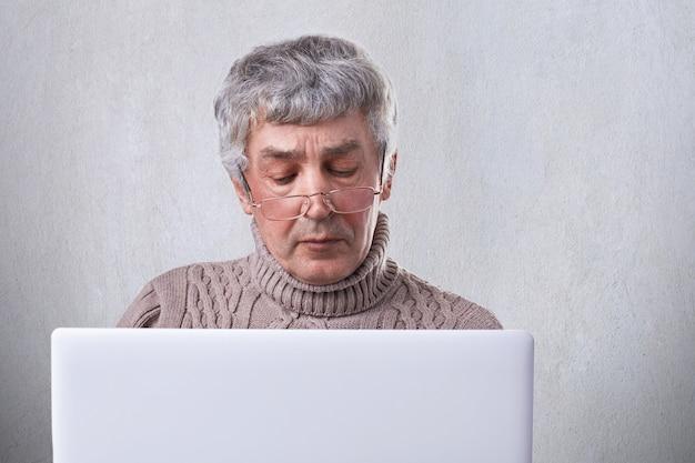 Starszy mężczyzna o siwych włosach i zmarszczkach skupił się na ekranie swojego laptopa. zadumany dorośleć mężczyzna w eyeglasses pracuje z komputerem z interneta radiem odizolowywającym nad bielem