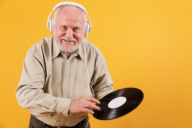 Starszy mężczyzna o wysokim kącie z nagraniami muzycznymi