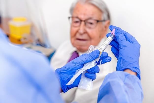 Starszy mężczyzna obserwujący go jako pielęgniarka, ubrany w kamuflowany kombinezon ochronny i niebieskie rękawiczki sanitarne, zapisuje swój test na koronawirusa.