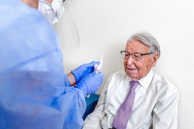 Starszy mężczyzna obserwujący pielęgniarkę ubraną w kombinezon ochronny na koronawirusa przygotowuje test na koronawirusa przed jego wykonaniem.