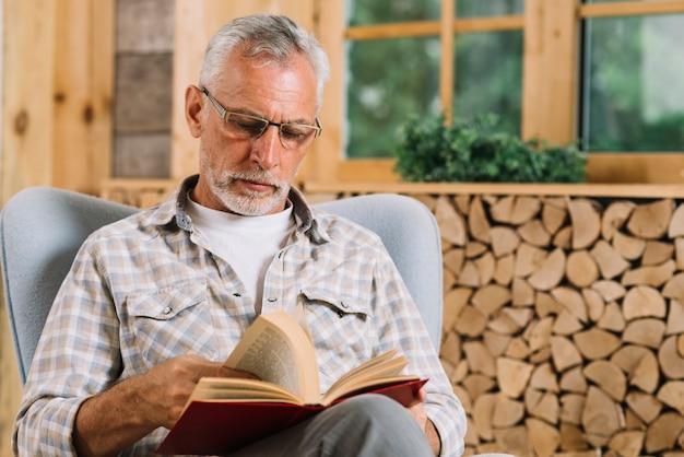 Starszy mężczyzna obsiadanie na ręki krzesła czytelniczej książce