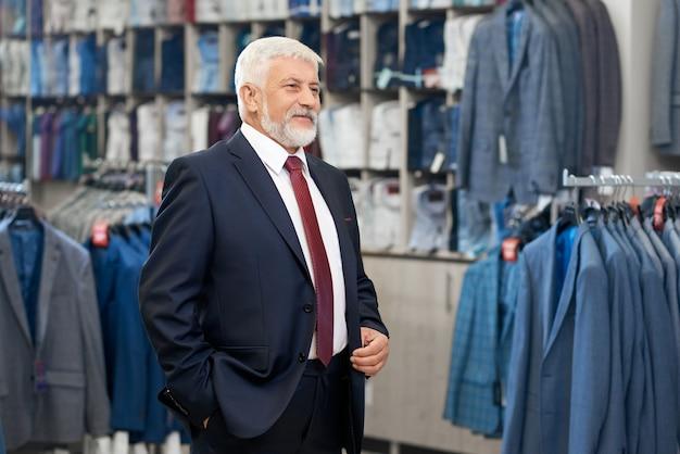 Starszy mężczyzna odbiera garnitury w sklepie.