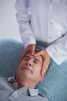 Starszy mężczyzna odbiera masaż głowy od fizjoterapeuty