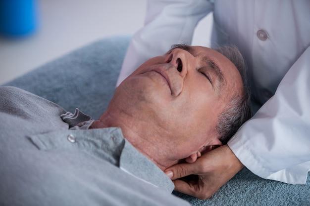 Starszy mężczyzna odbiera masaż szyi od fizjoterapeuty