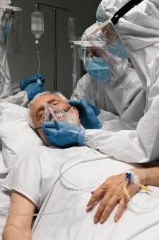 Starszy mężczyzna oddychający ze specjalnym sprzętem w szpitalu