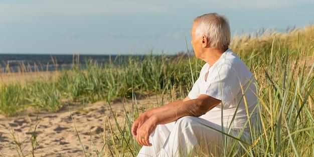 Starszy mężczyzna, odpoczynek na plaży i podziwianie widoków