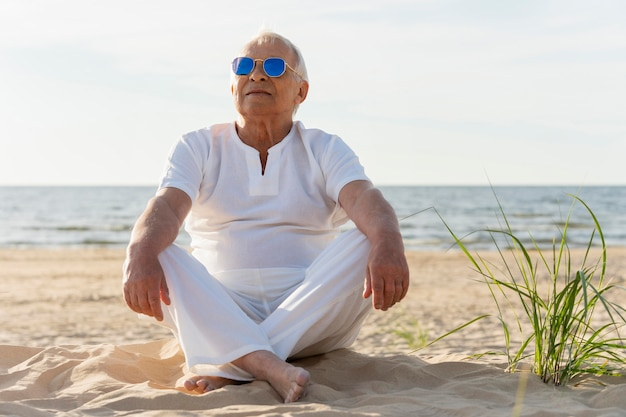 Starszy mężczyzna odpoczywa na plaży z okularami przeciwsłonecznymi