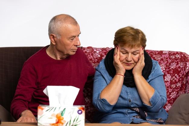Starszy mężczyzna opiekujący się chorą żoną, która cierpi na bóle głowy