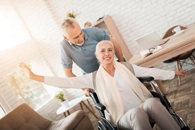 Starszy mężczyzna opiekuje się dojrzałą kobietą na wózku inwalidzkim.