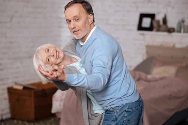 Starszy mężczyzna opierając swoją starszą żonę podczas tańca z nią w domu.