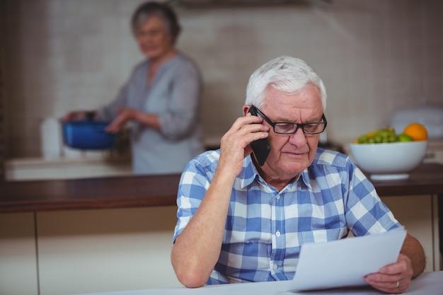 Starszy mężczyzna opowiada na telefonie komórkowym z żoną w tle