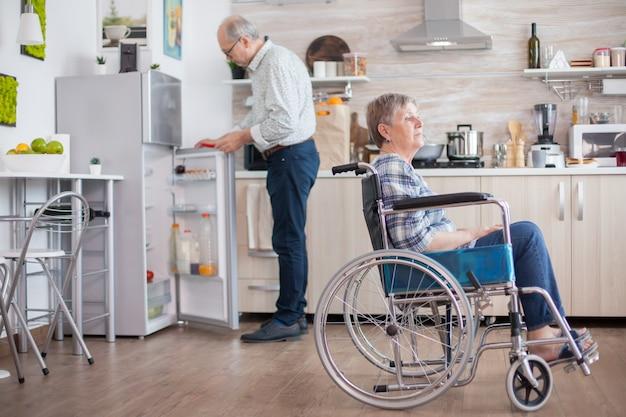Starszy mężczyzna otwiera lodówkę, podczas gdy jego niepełnosprawna żona siedzi na wózku inwalidzkim w kuchni patrząc przez okno. mieszkanie z osobą niepełnosprawną. mąż pomaga żonie z niepełnosprawnością. starsza para