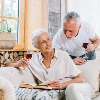 Starszy mężczyzna patrzeje jej żony obsiadanie na kanapie z książką