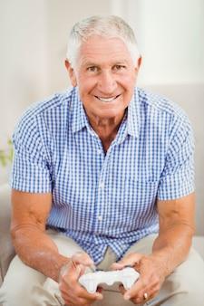 Starszy mężczyzna patrzeje kamerę i ono uśmiecha się w żywym pokoju z joystickiem