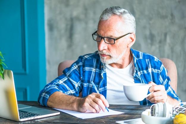 Starszy mężczyzna patrzeje laptopu mienia pióro robi notatkom