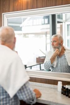 Starszy mężczyzna patrzeje lustro w fryzjera męskiego sklepie