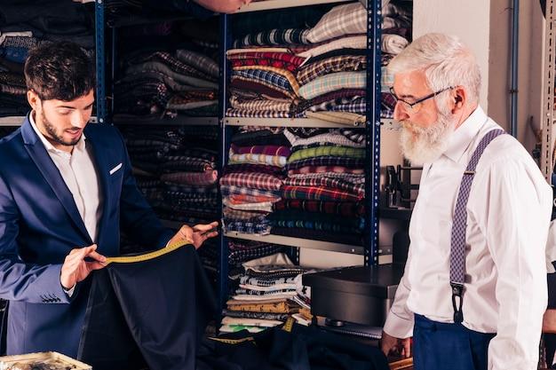 Starszy mężczyzna patrzeje męskiego projektanta mody bierze pomiar tkanina