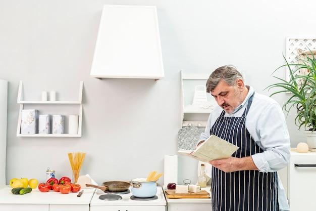 Starszy mężczyzna patrzeje w książce kucharskiej