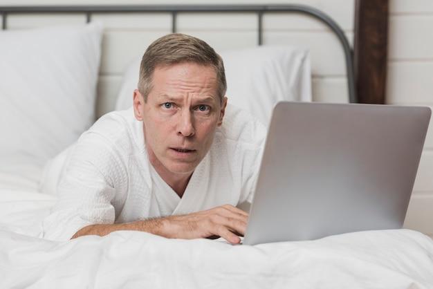 Starszy mężczyzna patrzeje zaniepokojony na jego laptopie w łóżku
