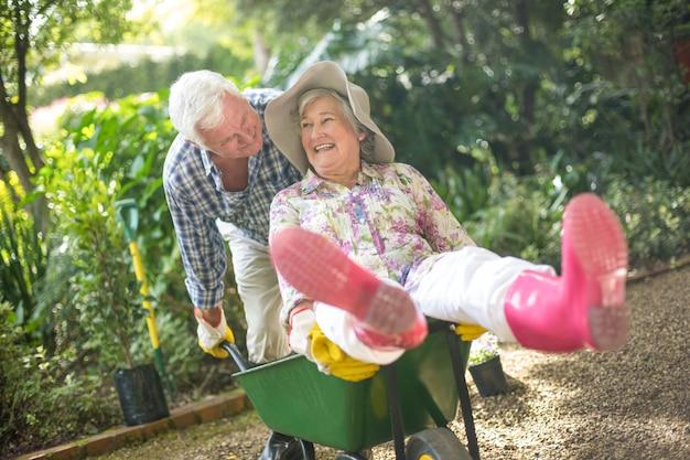 Starszy mężczyzna pchania żony, siedząc na taczki