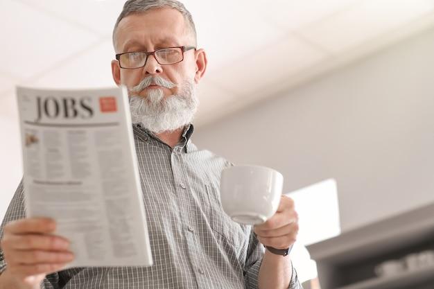 Starszy mężczyzna pije kawę podczas czytania gazety w domu