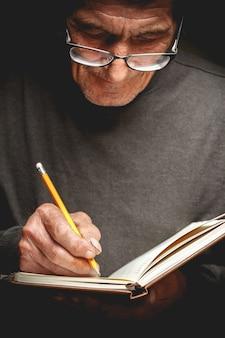 Starszy mężczyzna pisał ołówkiem w zeszycie