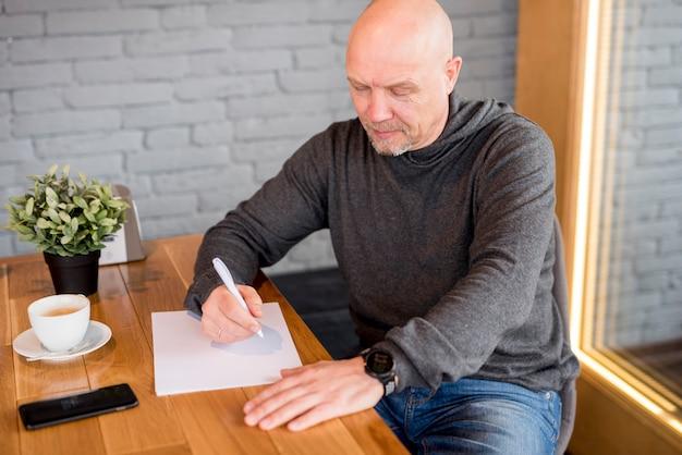 Starszy mężczyzna pisze na papierze