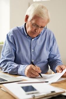 Starszy mężczyzna pisze raport podatkowy